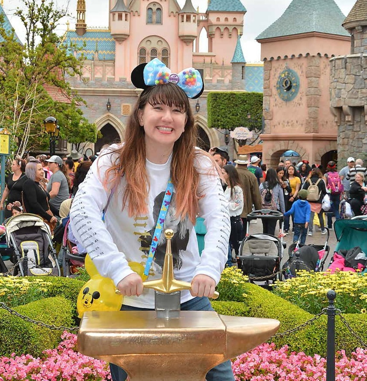 A woman tries to pull out the sword in the stone at Disneyland.