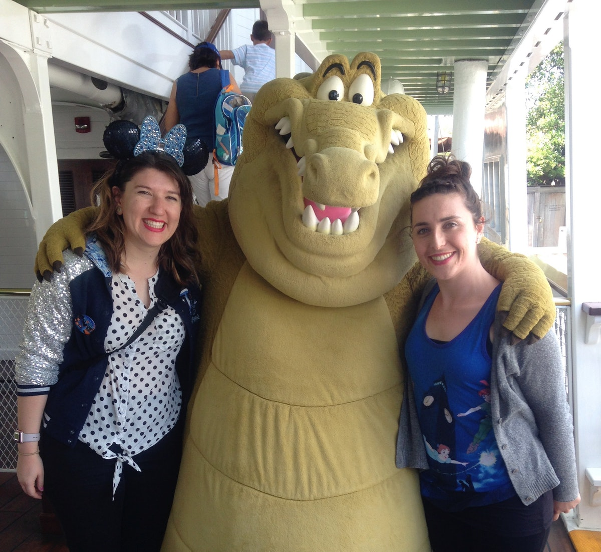 Two women pose for a pic with Louis the alligator from 'The Princess and the Frog' on the Mark Twain Riverboat at Disneyland.