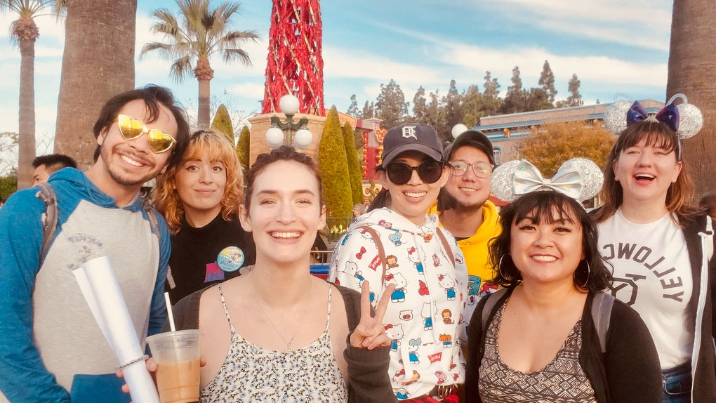 A big group of friends in Mickey Mouse ears smile and pose together at Disneyland.
