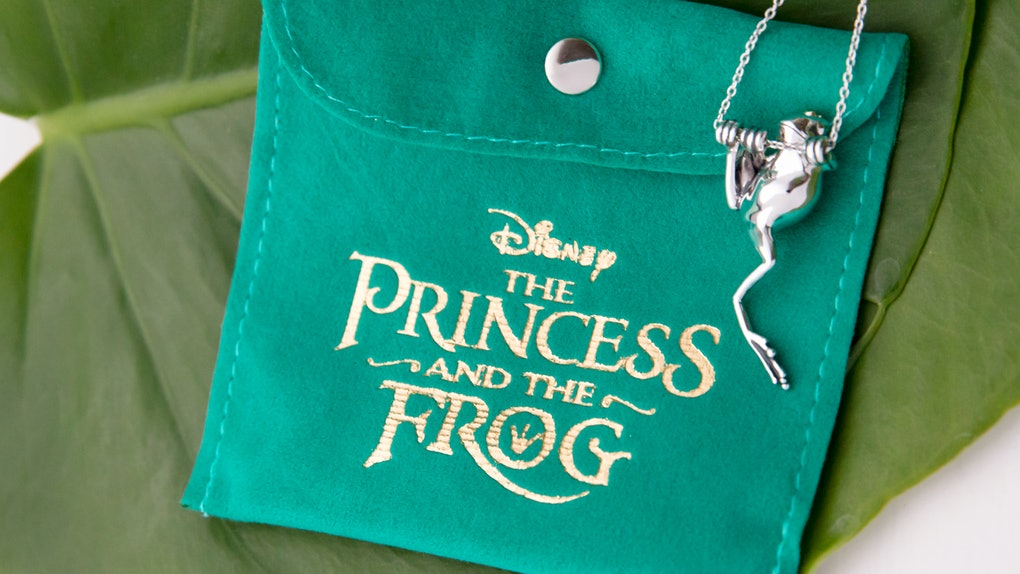 A frog necklace from Disney's 'The Princess and the Frog' jewelry collection by RockLove dangles off a green patch sitting on a lily pad.