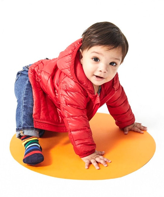 a baby wearing a red puffer jacket from primary