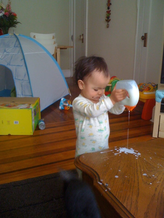 a toddler girl pouring glue on a table
