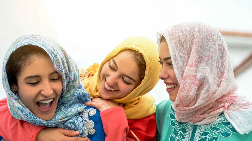 Three women in headscarves smiling