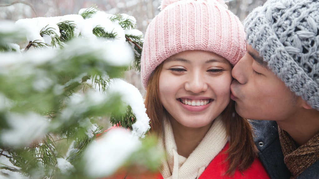 Young Asian couple kiss in snow