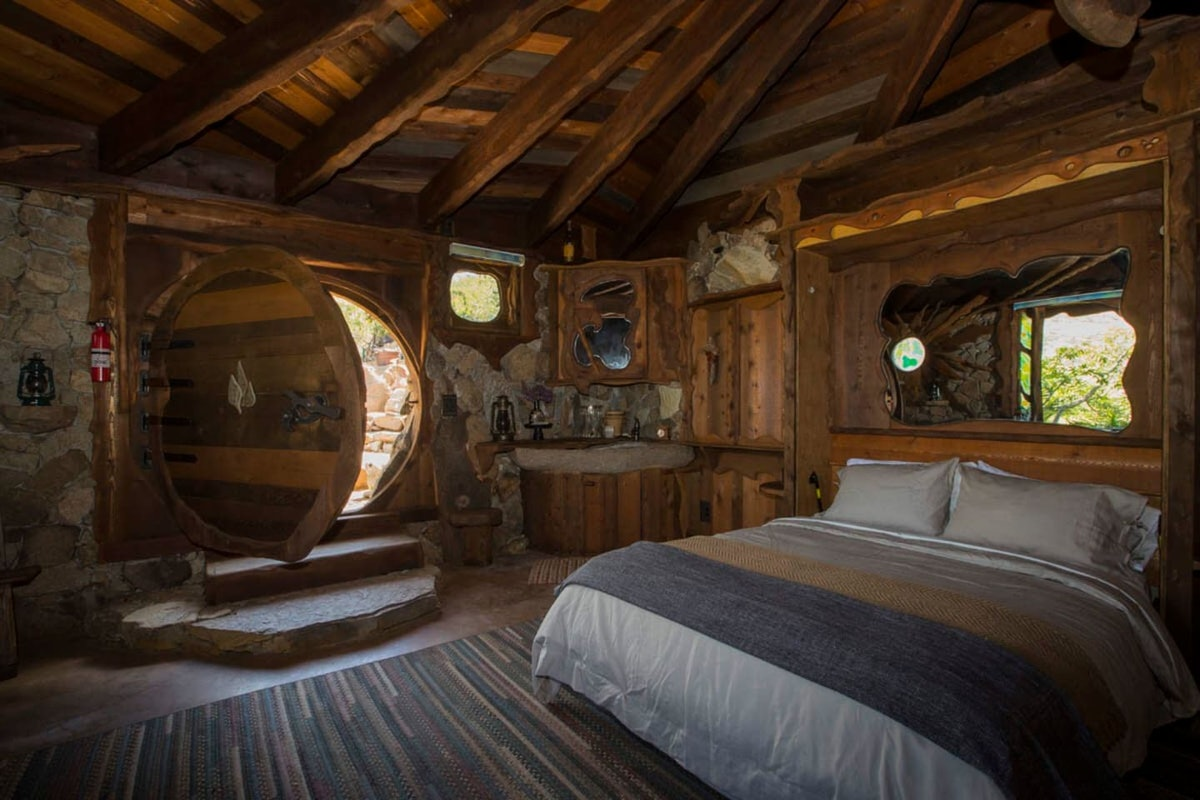 A secluded 'Hobbit' inspired home on Airbnb has lots of wood details and a bed right near the front door.
