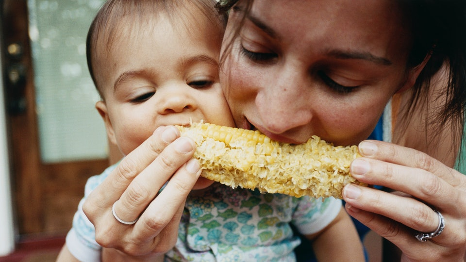 A mom and toddler share a corn cob