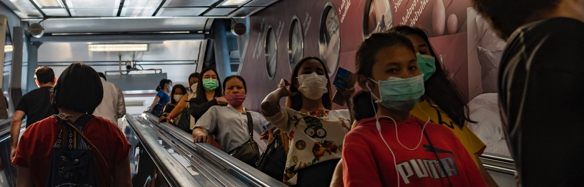 People walk while wearing protective face masks due to concern over the spread of coronavirus in Bangkok, Thailand, on February 6, 2020.
