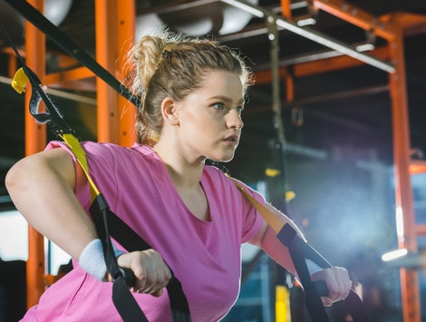 A person in a pink t-shirt and white wristbands performs a TRX pushup. Getting back to the gym after you're been sick can be tough, but listening to your body is key, experts say.