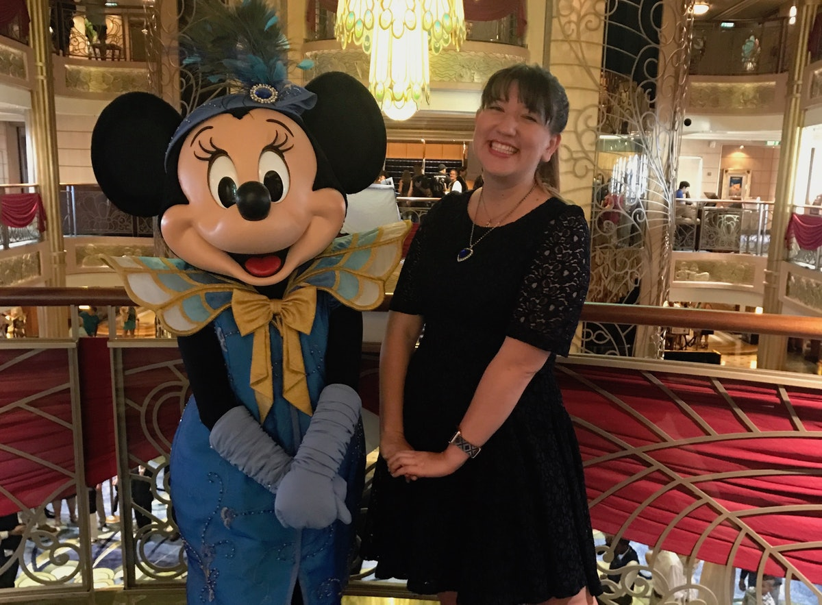 A woman and Minnie Mouse in formal wear pose in the atrium of the Disney Cruise ship.