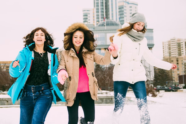 Three women leaping for joy in snow