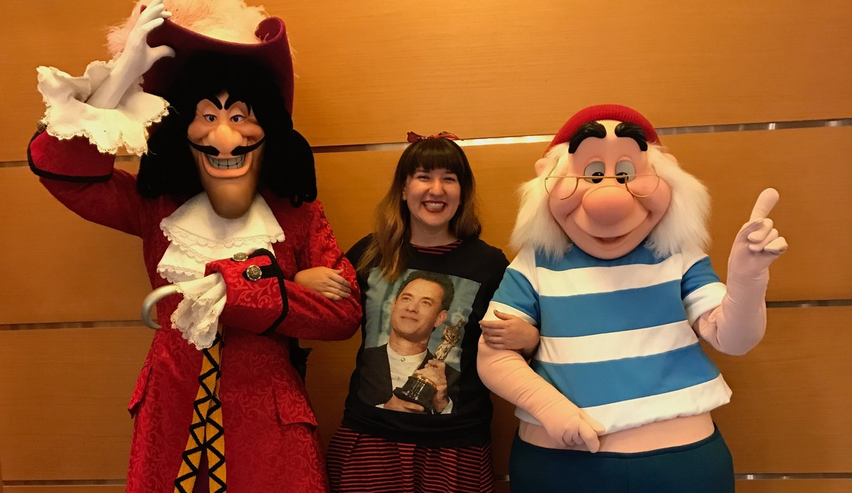 A woman smiles with Captain Hook and Mr Smee on the Disney Cruise.