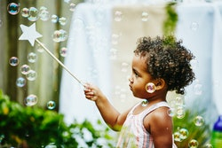A young girl pops bubbles