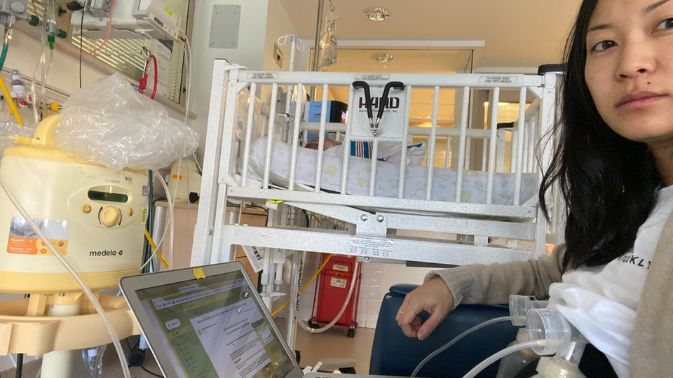 A mom pumps milk in a NICU while on her laptop