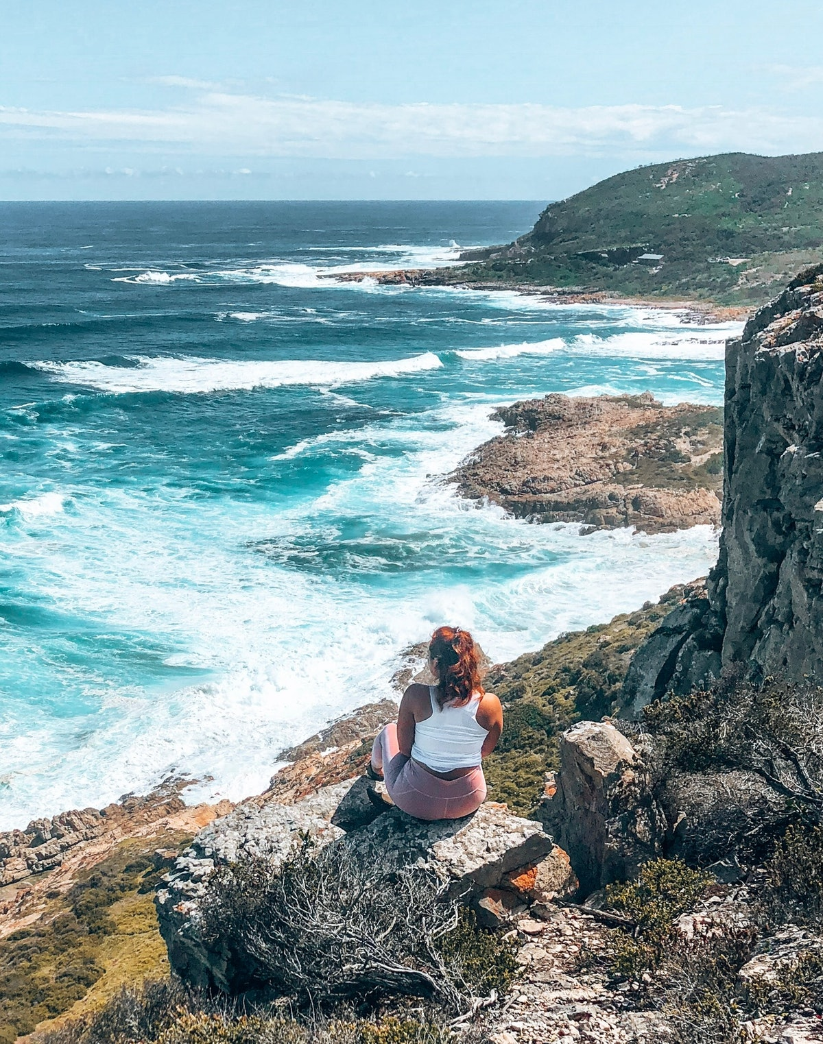 A woman dressed in workout attire sits on a rock and looks out at the ocean below.