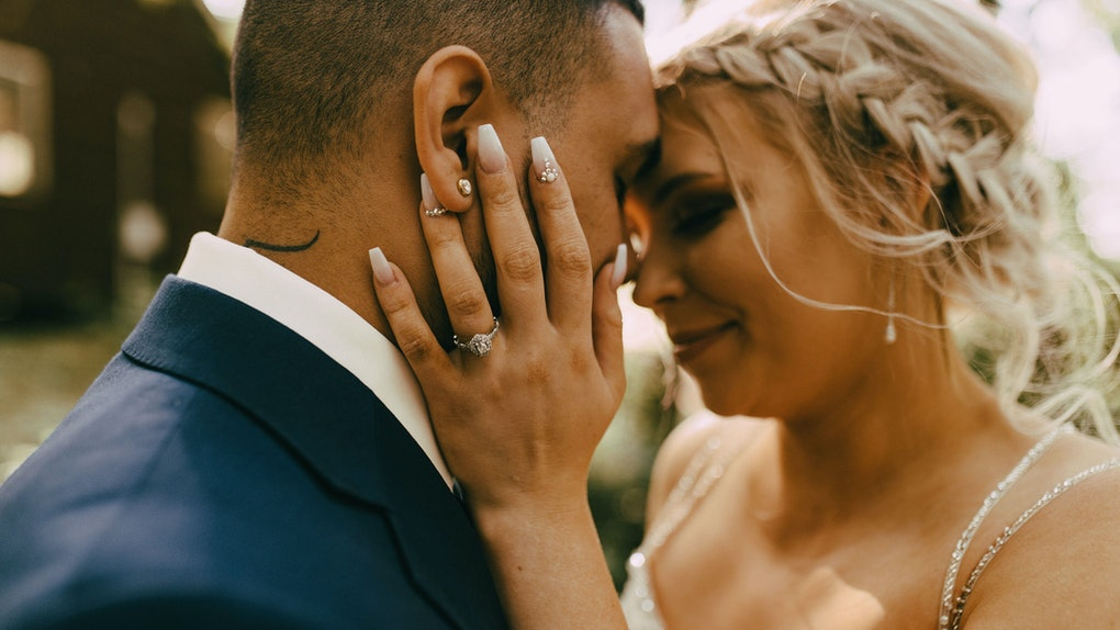 A couple embraces each other on their wedding day while dressed up and standing outside a cozy home.