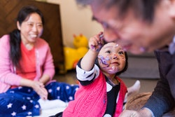 a young girl paints her grandfather's face