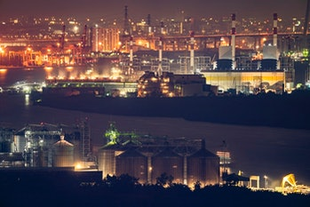 Aerial view of industrial area, factory, port and harbour in Bangkok city, Thailand at night time.