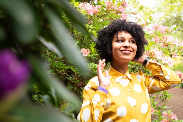 Young black woman in the park with flowers