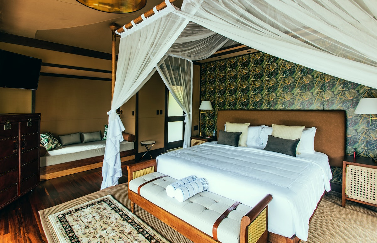 A suite at Nayara Tented Camp in Costa Rica has lots of natural light, a luxurious bed, and rainforest-inspired decor.