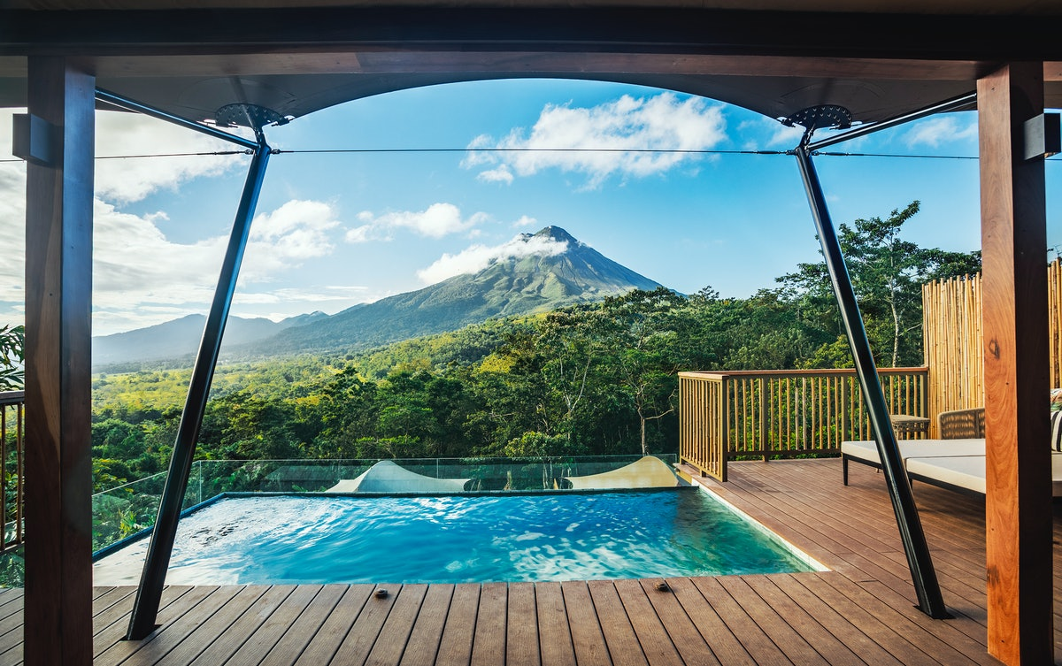 Nayara Tented Camp features a luxurious pool on a deck that overlooks the volcanoes and green mountains of Costa Rica.