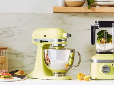 "KitchenAid mixer and blender in ""Kyoto Glow"" on a counter top surrounded by nuts, veggies, fruits, and smoothies in complementing colors"