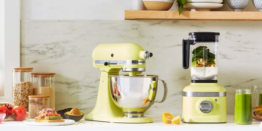 """KitchenAid mixer and blender in """"Kyoto Glow"""" on a counter top surrounded by nuts, veggies, fruits, and smoothies in complementing colors"""