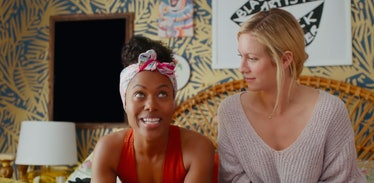 Two best friends sit on a bed in a colorful room and chat in 'Someone Great' on Netflix.