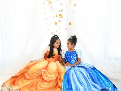 Two girls wearing Disney Blankie Tails, one in Belle gown the other in Cinderella gown