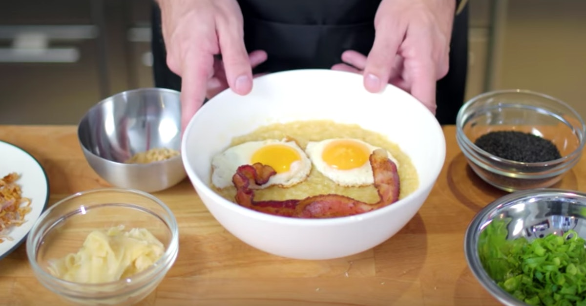 A pair of hands holds onto a bowl of congee inspired by Disney's 'Mulan,' with a smiling bacon and egg face and ingredients all around.