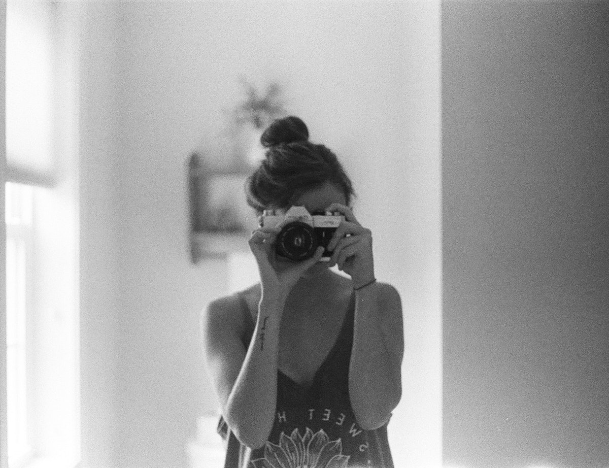 A woman takes a selfie with a film camera while standing in her bathroom.