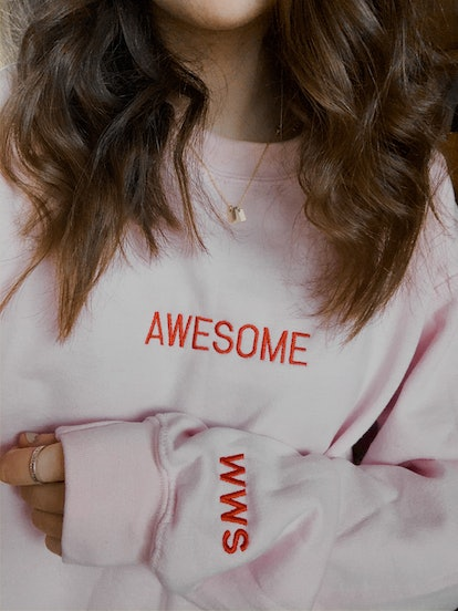 """A young woman poses in a light pink sweatshirt that says, """"Awesome."""""""