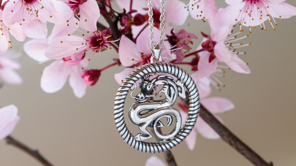 A Mushu necklace from the 'Mulan' RockLove Jewelry collection hangs from a magnolia flower branch.