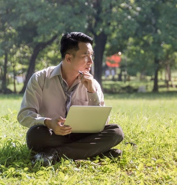 Businessman sitting on the lawn Using a notebook In researching information data analysis And planni...