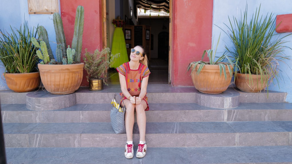 A woman dressed in a colorful dress and sneakers smiles while sitting on steps in Mexico City.
