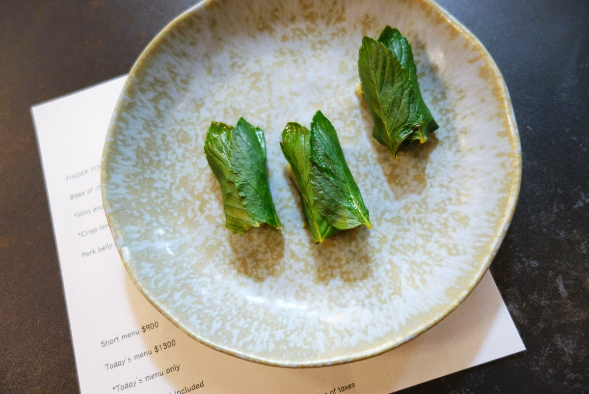 A neutral colored plate has three pieces of spearmint mochi at a restaurant in Mexico City.