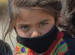 A young girl wearing a facemask amid concerns over the spread of the COVID-19 novel coronavirus sits on a motorbike with her father on the outskirts of Islamabad on March 18, 2020.