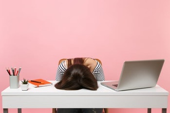 Young frustrated exhausted woman laid her head down on the table sit work at white desk with contemp...
