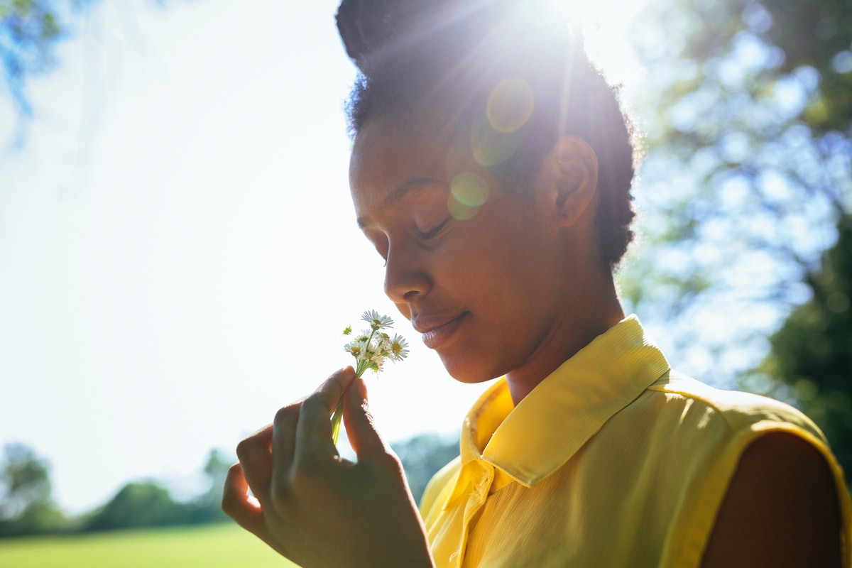 Portrait of smiling young woman smelling flowers