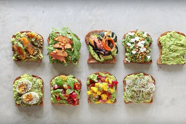 Various avocado toasts with different toppings all sit on a kitchen counter for lunch.