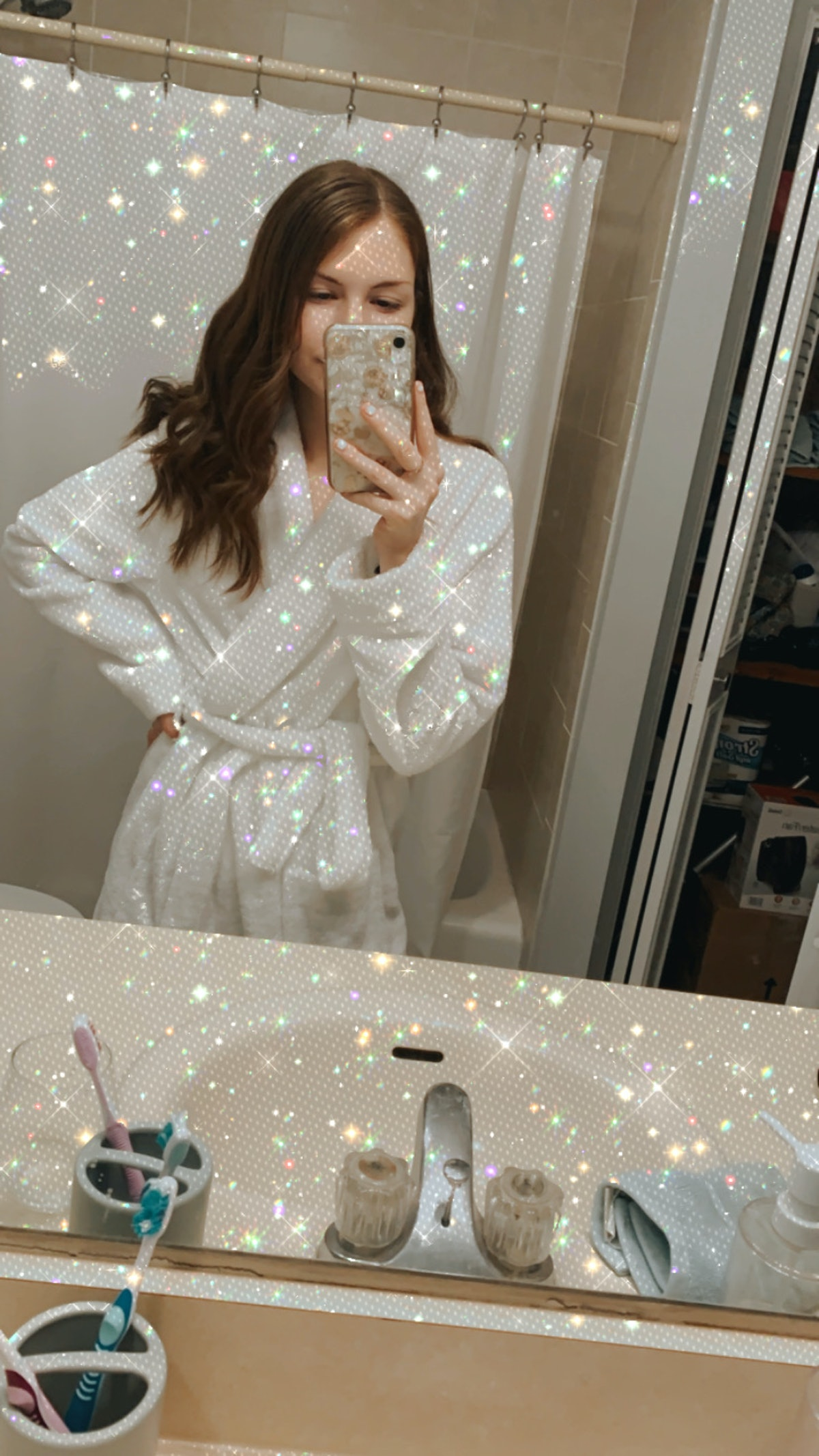 A young woman in a bathrobe poses for a selfie while using a glitter on white effect.