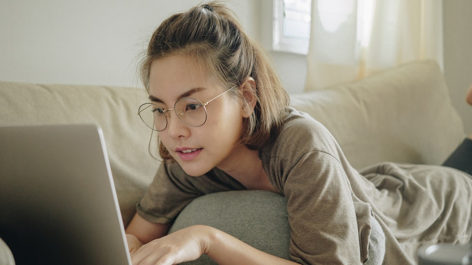A woman works from home, typing on her laptop while lying on the couch. This article outlines how to work from home if you've never done it before.
