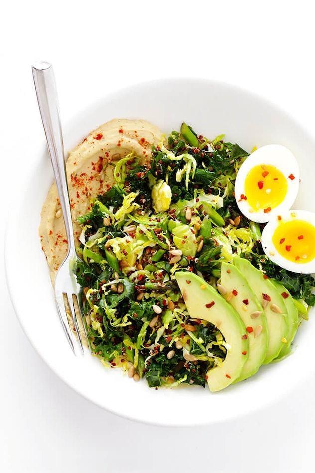 A bowl of greens, hummus, and hard boiled eggs.