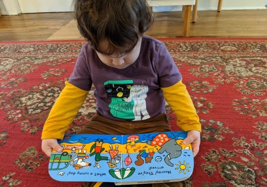 photo of toddler with book in hand