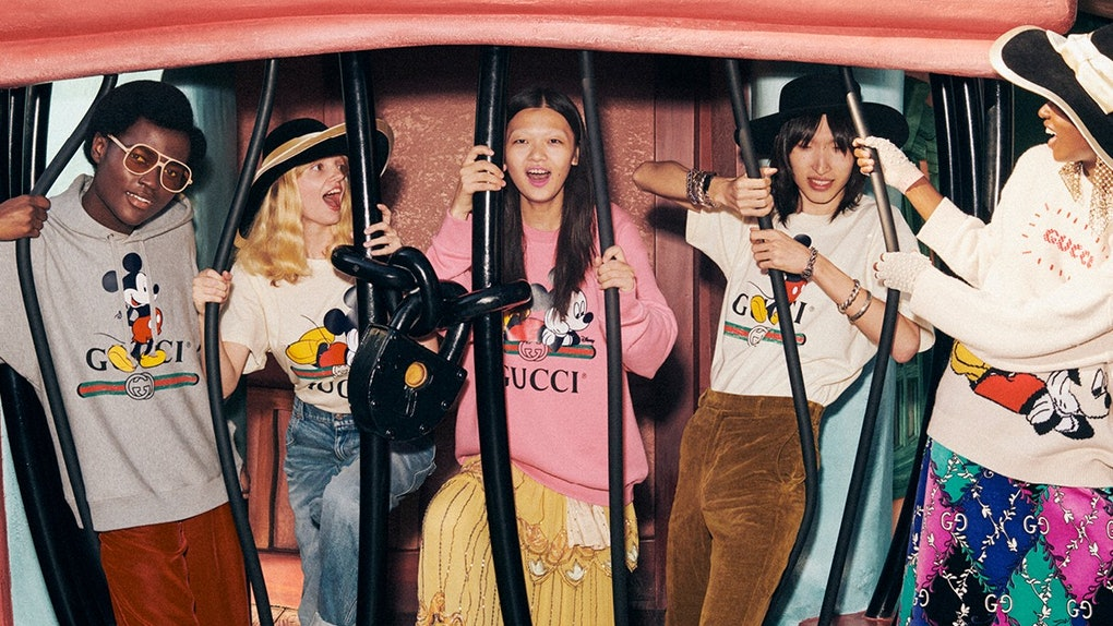 A group of friends wearing the Disney x Gucci collection laugh while standing in Toontown at Disneyland.