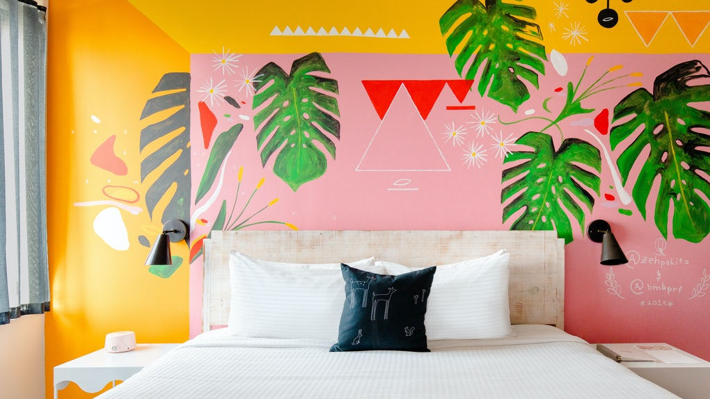 A custom mural room at Quirk Hotel in Richmond, Virginia features tropical palm leaves and bright colors.