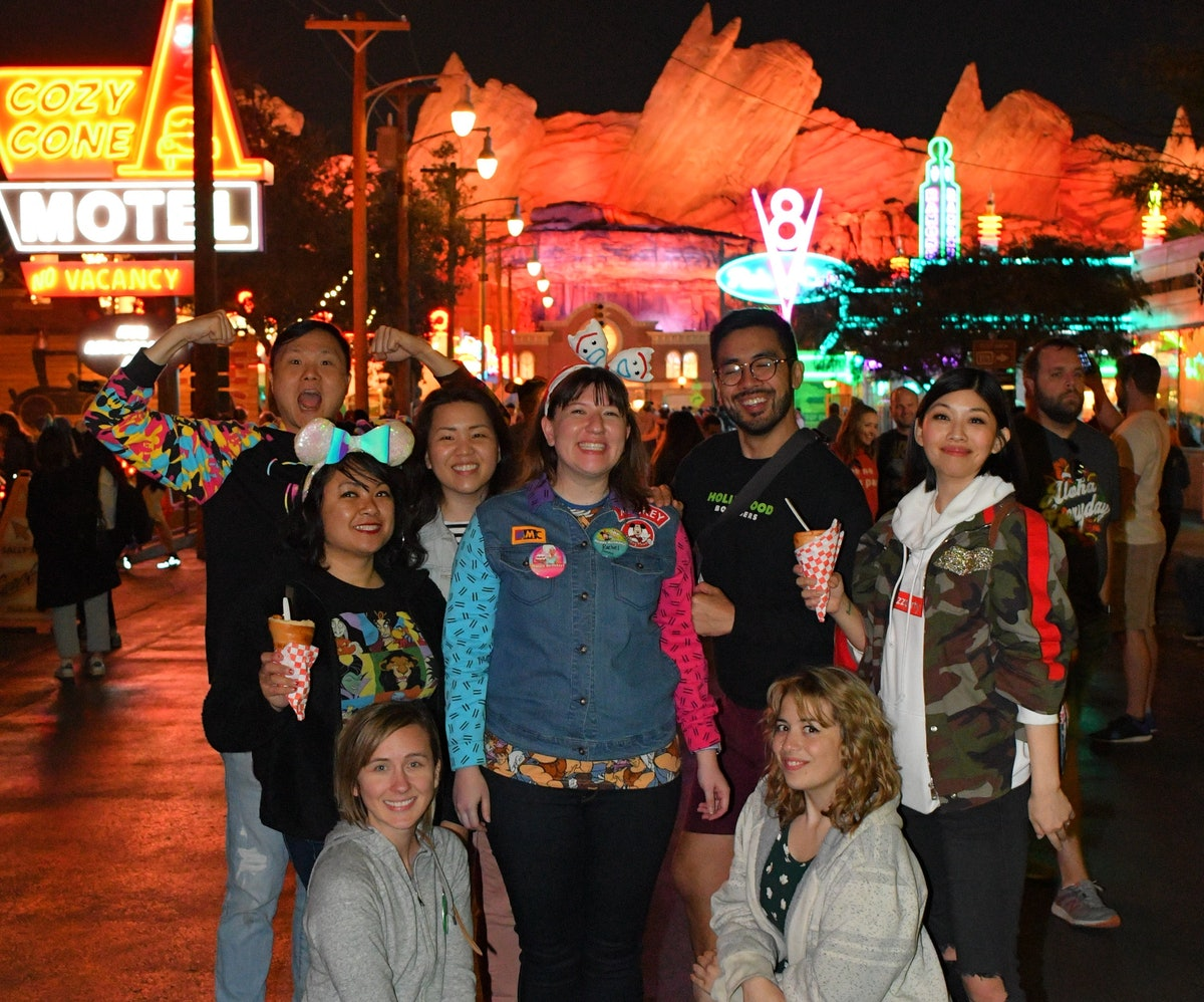 A group of friends stand together and pose in the middle of Cars Land at Disneyland.