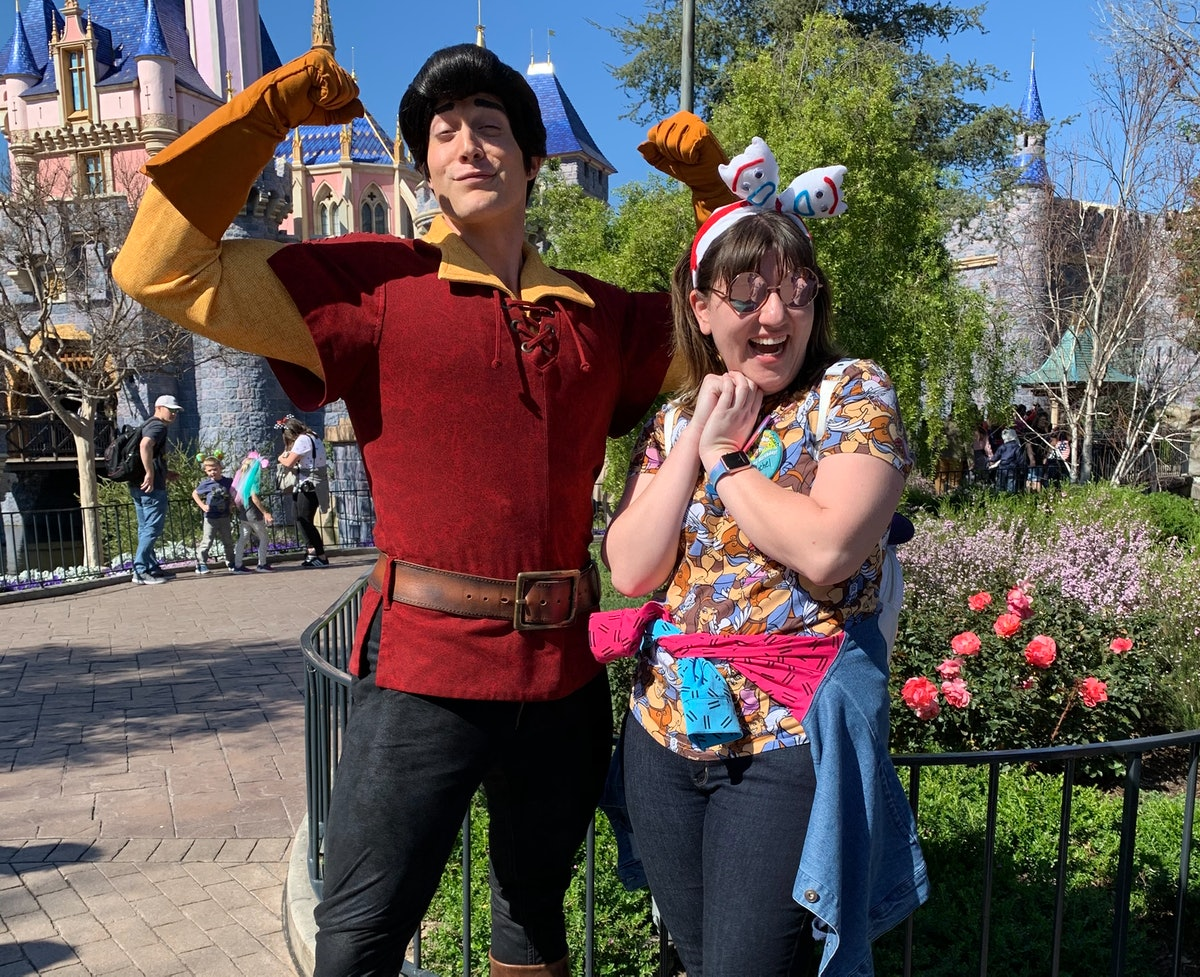 A woman with a jacket tied around her wait poses with Gaston from 'Beauty and the Beast' in front of...