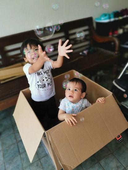Children catch bubbles inside a cardboard box