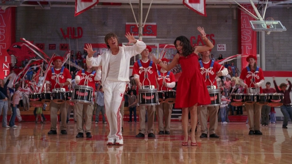 """Zac Efron and Vanessa Hudgens dance to """"We're All In This Together"""" From Disney Channel's 'High School Musical' with a marching band behind them."""