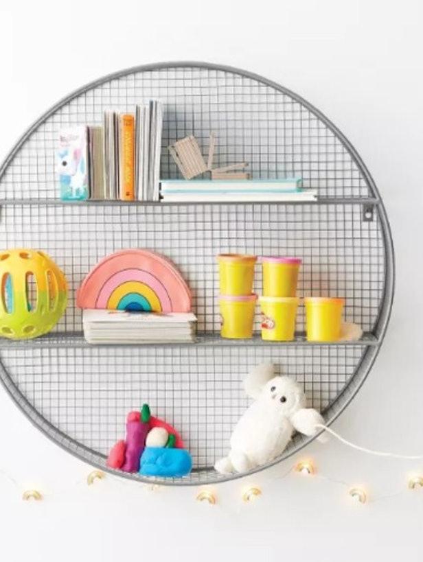 Grey round metal shelf with various kids toys displayed